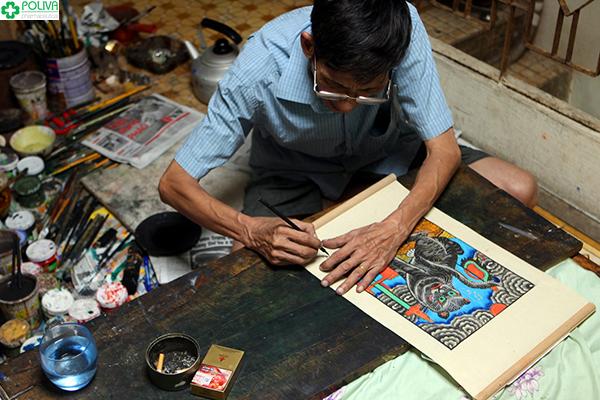 Một nghệ nhân đang làm tranh ở Làng Hồ.
