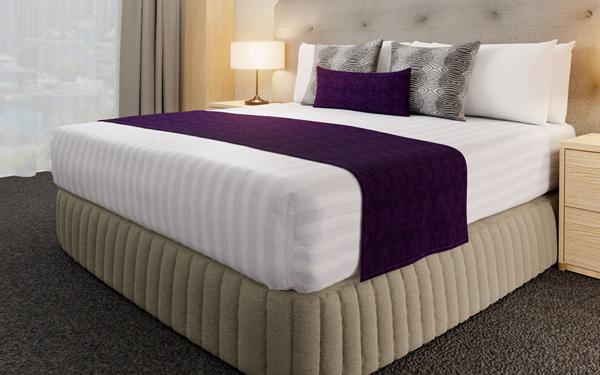 Mảnh vải trải giường màu đậm tạo sự nổi bật cho cả chiếc giường khách sạn