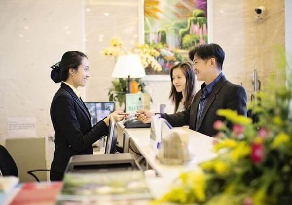 Nhân viên lễ tân làm thủ tục check-out cho khách hàng