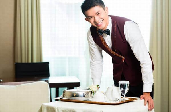 Nhân viên room service phục vụ đồ ăn cho khách hàng