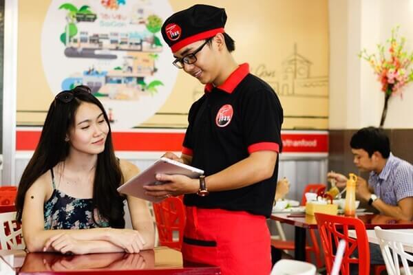 Nhân viên phục vụ tự tin và chuyên nghiệp trong trang phục của nhà hàng