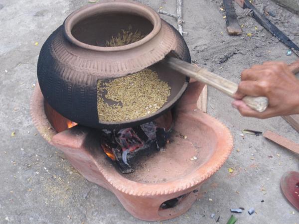Công đoạn rang lúa trong chiếc niêu đất, rang thật nhỏ lửa để không bị cháy mà cốm vẫn giữ được vị dẻo
