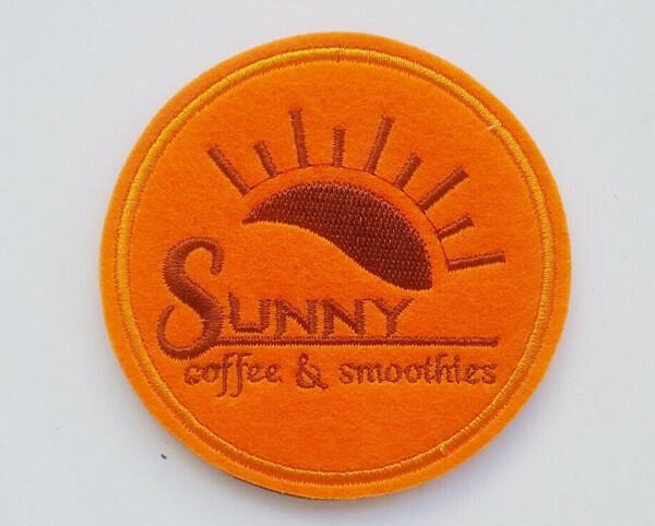 Lót ly vải nỉ màu cam của Sunny Coffee với những tia nắng tỏa ra gây ấn tượng với mọi người