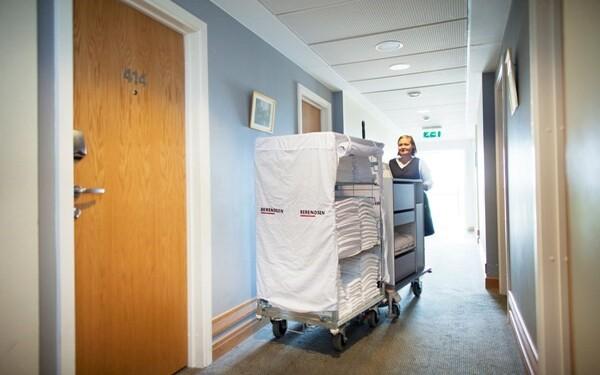 Nhân viên buồng phòng chuẩn bị xe đẩy dựng dụng cụ trước khi vào làm phòng
